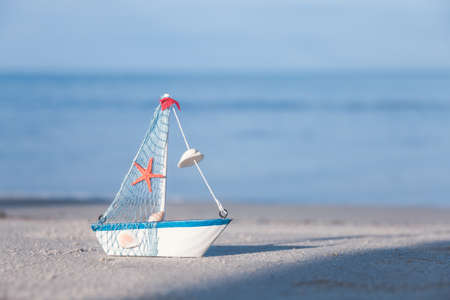 The toy sailboat is on the beach in the morning sunshine. Summer holiday travel concept