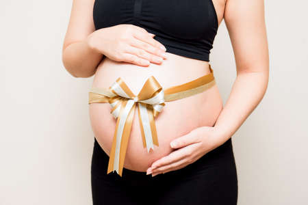 Close up image of pregnant woman belly with gold ribbon. A mother waiting for the baby.