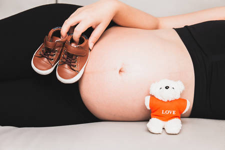 Pregnant woman sleep on the sofa and hand holding small baby shoes near her belly. A mother waiting for the baby.