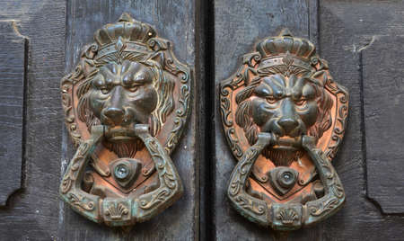 ancient wooden gate with door knocker rings photo