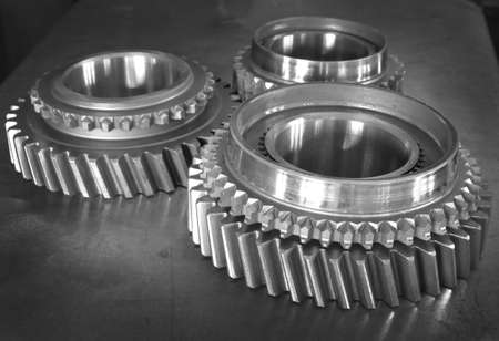Three metal gears on plain background photo