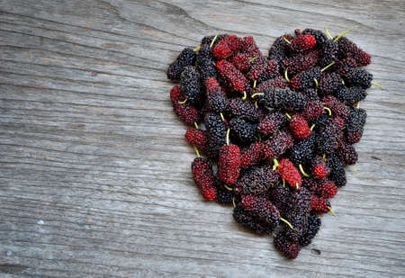 Shape of heart made of mulberry on wooden table