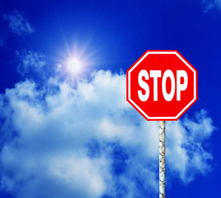 Red Stop Sign with Blue Sky and Clouds Background photo
