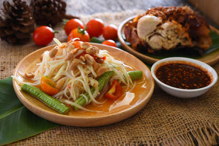 Papaya salad with fried chicken and vegetables, Som Tum, Traditional Thai food.