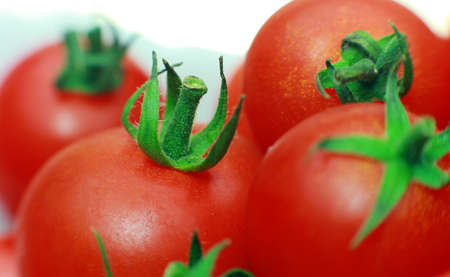 ripe tomatoes close-up. On the plate are tomatoes in the background Stock Photo