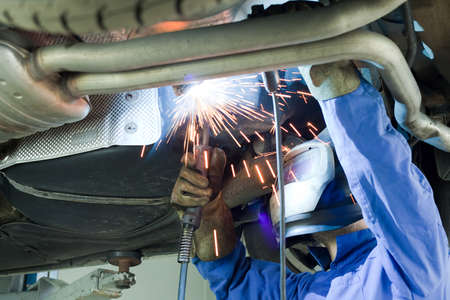 Mechanic cuts off the muffler in the car.
