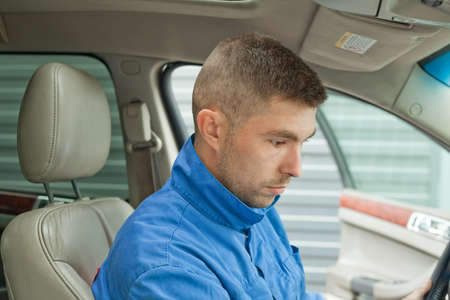 A repairman dressed in a work uniform is in the car and checks the gearbox and dashboard