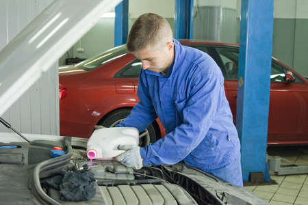 filling the car with antifreeze. Master in the workshop opens the tank and pours pink coolant