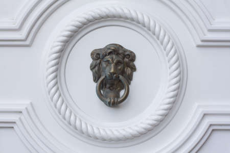 Lion head door knocker on the white door  photo