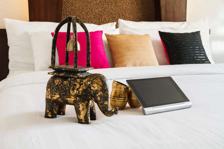 decorate mobile telephone: Tablet and elephant decoration on white bed