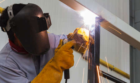 erecting: Welder in position over head action in steel structure factory. Stock Photo