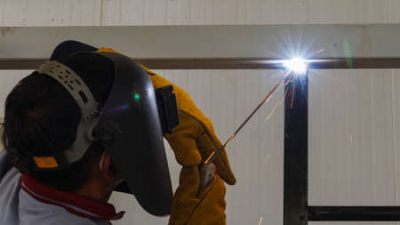 steel head: Welder in position over head action in steel structure factory. Stock Photo