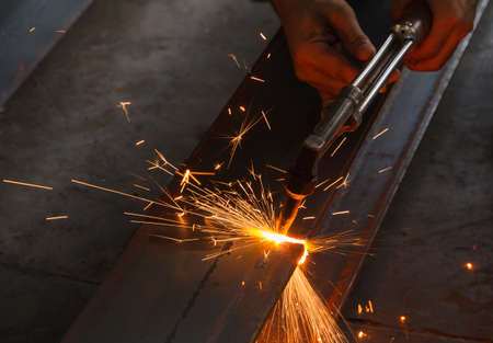 Closeup metal cutter, steel cutting with acetylene torch, industrial worker on manufacturing area.