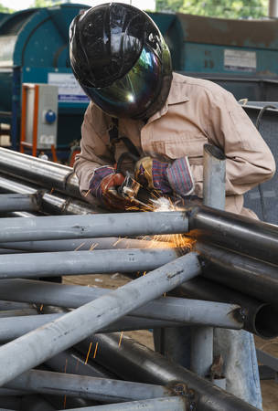 Worker with safety equipments and protective mask welding steel structure in construction factory - Use the wrong kind equipment.