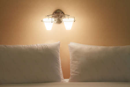 Close up of a bed and pillow with lamp light, Vintage style. Stock Photo