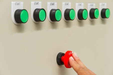 Finger touch on red emergency stop switch and reset button.