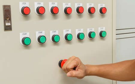 Fist smash touch on red emergency stop switch and reset with green start buttons.