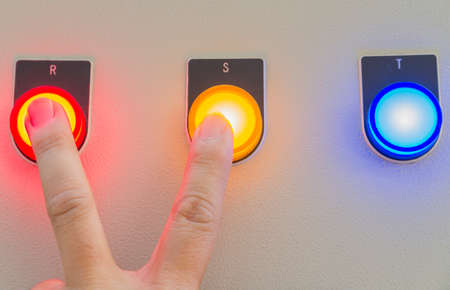 Forefinger and middle finger touch on red and yellow buttons.