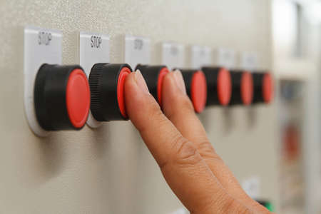 Forefinger and middle finger touch onred stop buttons.
