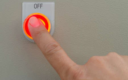 Forefinger touch on red off button.