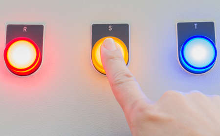 Forefinger touch on yellow stop button. Stock Photo