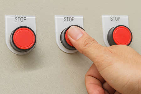 Thumb touch on red stop switch button.