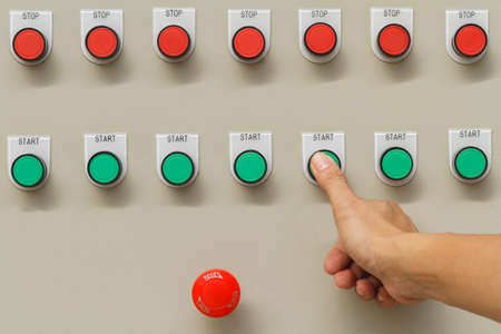 Thumb touch on green start button and red emergency stop switch.