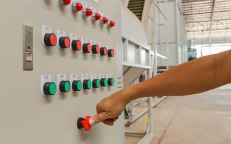Thumb touch on red emergency stop switch and green start buttons.