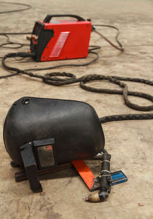 Old Welding Mask and Plasma Cutting Put on Dirty Floor of Factory. Stock Photo