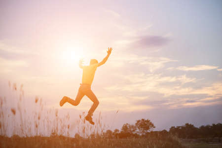 An adult man jumping in joyous at the coastline during sunset