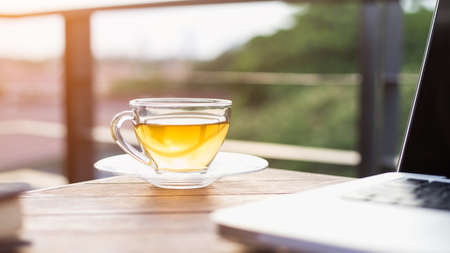 Tea in a cup besides a laptop computer on the table