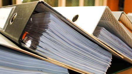 Arch file contenenti pagine di documenti, autorità, molte pile di cartelle di documenti in ufficio per file di rapporto annuale su Foto sfocata astratta di mani di uomo d'affari che lavorano con computer portatile. concetto di affari occupati Archivio Fotografico