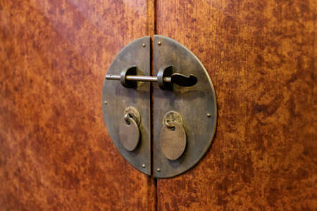 Vintage keyhole with key on vintage wooden cabinet, wood door handle locker Archivio Fotografico