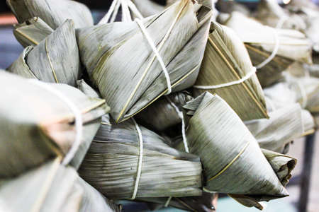 Chinese tradition food - steamed rice dumpling, Zongzi or Traditional Chinese Sticky Rice Dumplings, Traditional Dragon Boat Festival food concept unwrapping zongzi or rice dumpling. Asian food steamed sticky rice dumpling with fillings wrapped in reed leaves. Stock Photo