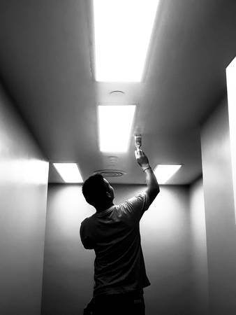 The black silhouette of the technician working on the ceiling, Workers are painting bright ceilings on large ceilings, Silhouette technician who painted the ceiling painted with fluorescent lighting