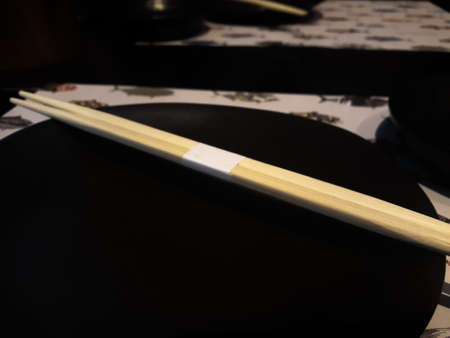 blur picture Chinese Chopsticks on a Empty Black plate for background, Empty black plate and wooden chopsticks on wooden desk
