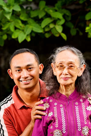 asian ethnic senior woman with young adult son