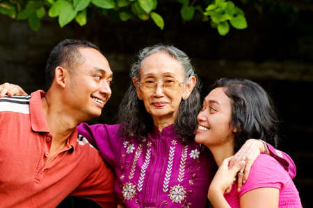 family portrait of asian ethnic senior mom with young adult son and daughter