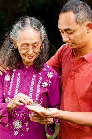 asian ethnic old woman taking pills helped by young adult son photo