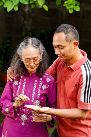 medicate: asian ethnic senior woman taking pills helped by young adult son