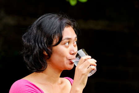 asian ethnic young adult female in thirst drink a glass of a pure mineral water photo