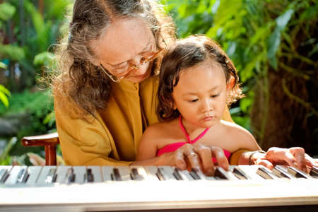 asian ethnic old female teaching child play piano photo
