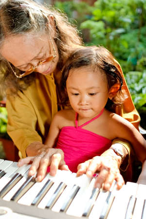 asian ethnic grandmother teach child playing piano photo
