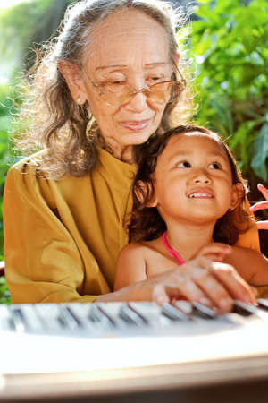 asian ethnic old woman teach child play piano photo