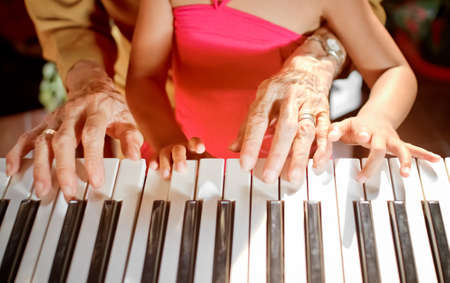 old piano: hands of old woman and child play piano together Stock Photo