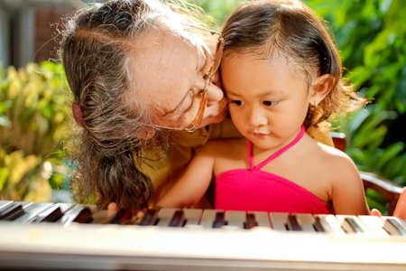 asian ethnic elderly woman love to teach child play piano photo