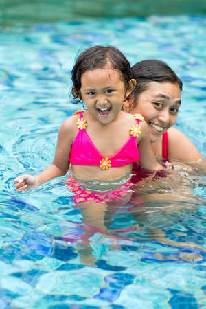 asian ethnic little girl and mother fun together in swimming pool together photo