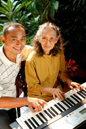 old piano: asian ethnic elderly mother play piano together with young man
