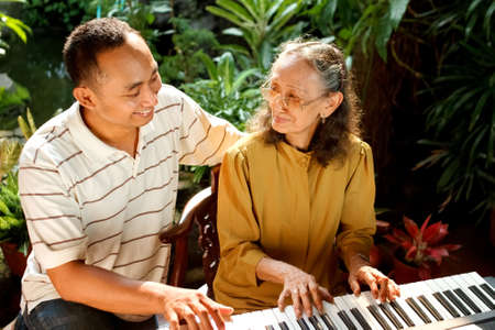 asian ethnic senior mother play piano with adult son Stock Photo