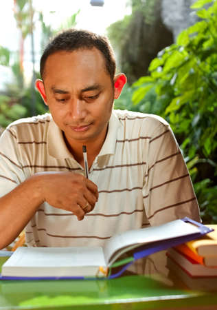 concentrate on: asian ethnic young man concentrate studying literature